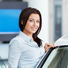 Woman in a dealership next to a car, smiling