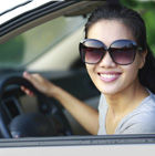 Woman looking out of a car window and smiling.