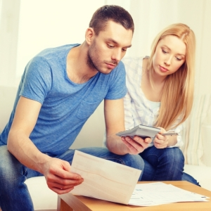 A couple looking at a stack of papers and a calculator.