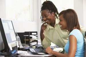 Two women smiling while looking at a computer screen.