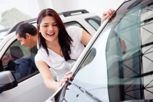 A woman smiling at a vehicle while car shopping in a dealership.