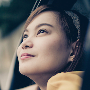 Close up of a woman looking out of a car window.
