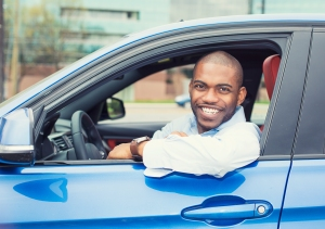 A man in a blue car, smiling at the camera.