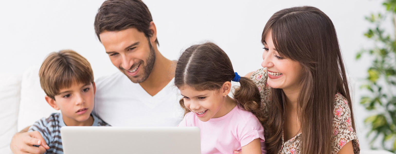 Family smiling and looking at a laptop.