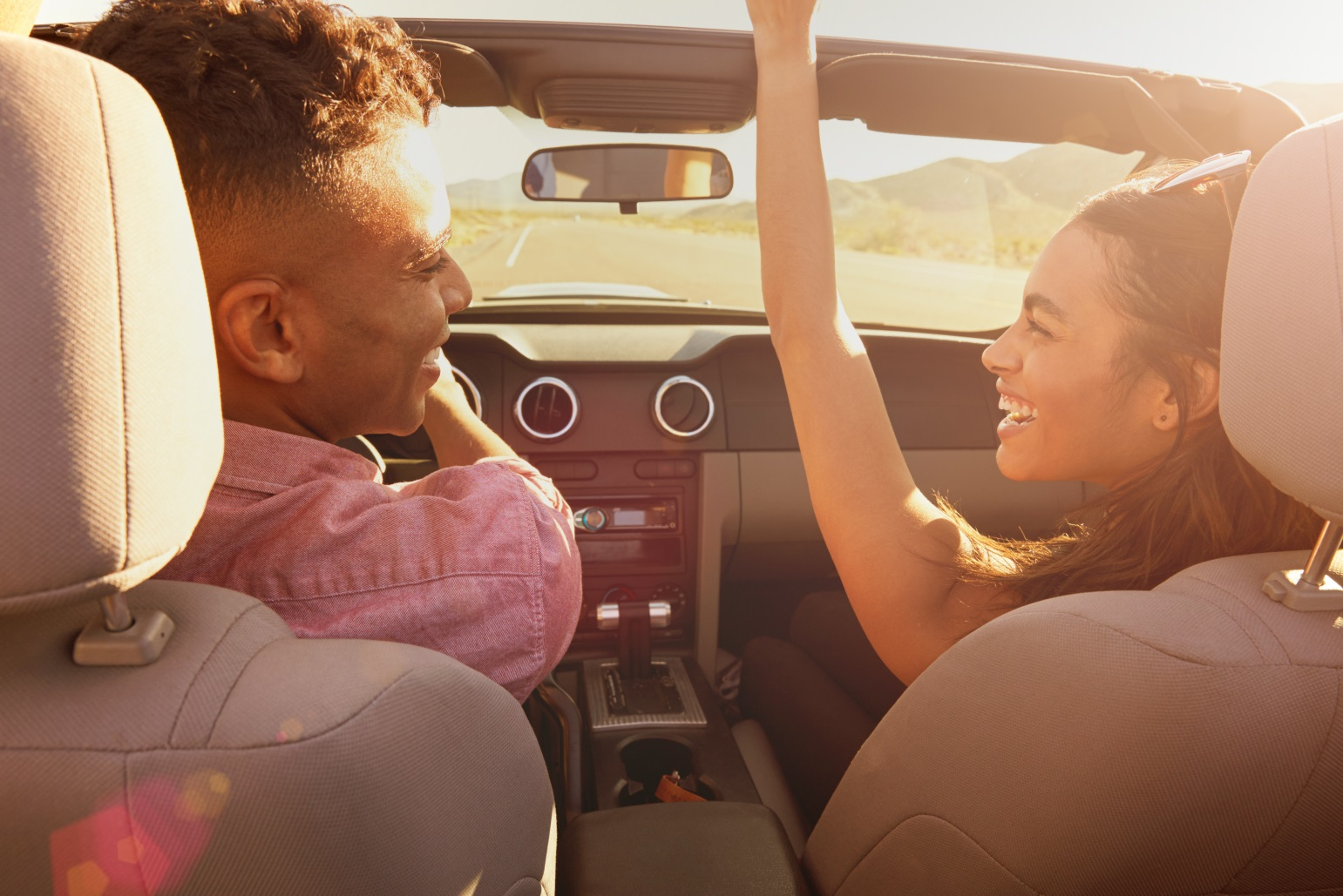 Man and woman smiling in convertible car