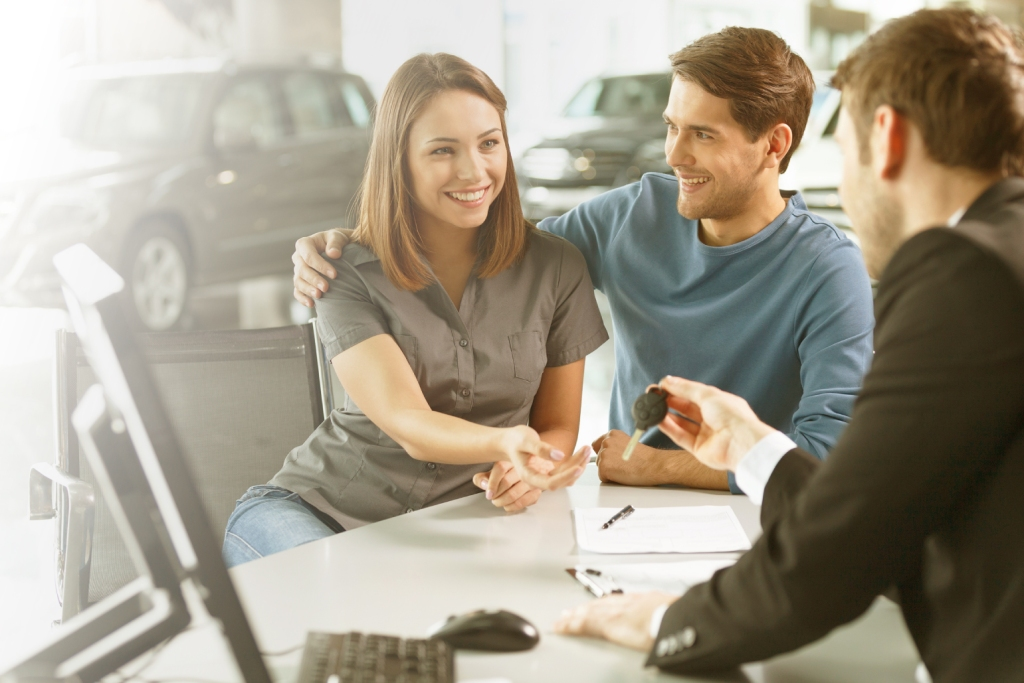 Young couple receiving car keys from dealer