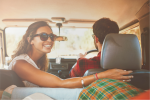 Smiling woman looking over shoulder from front seat of car