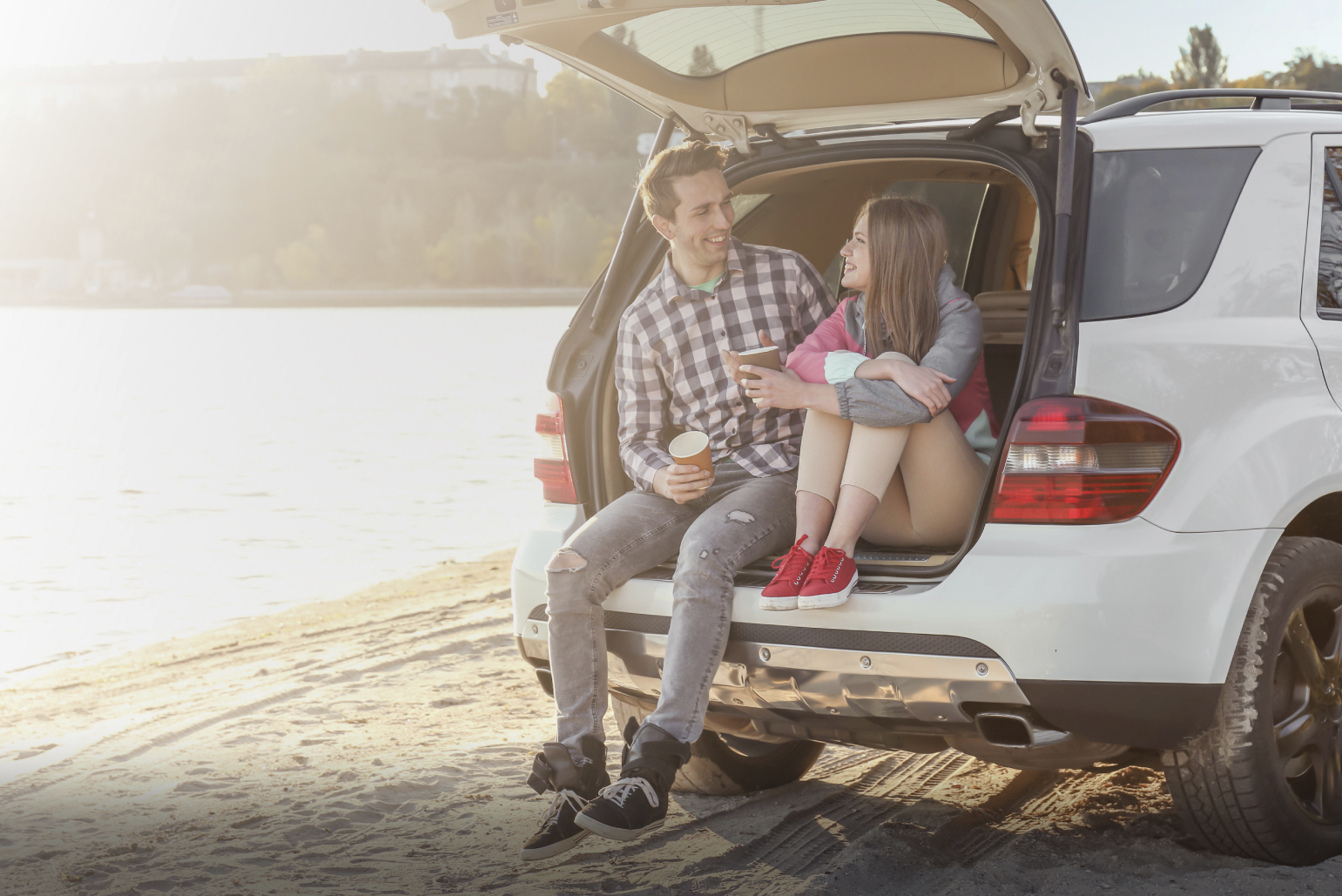 Man and woman first-time car buyers sitting on tailgate