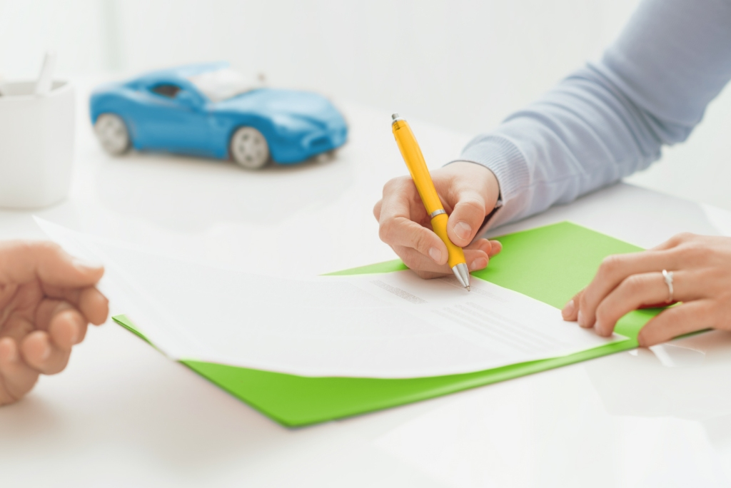 Woman signing paper to remove cosigner from car loan