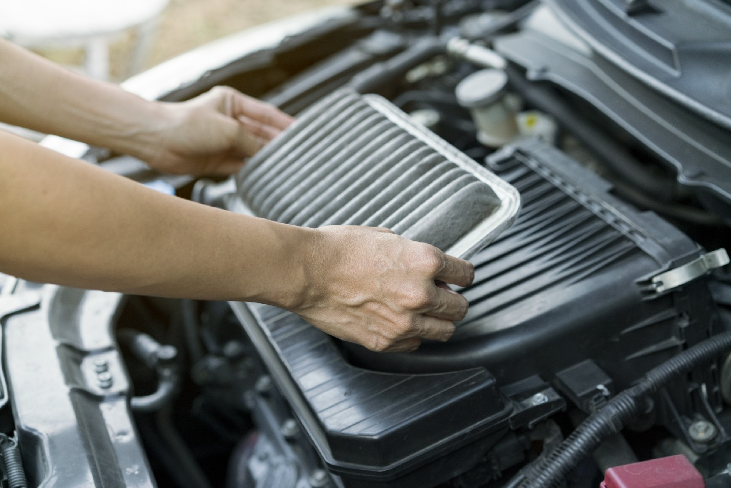 Man removing car air filter from engine