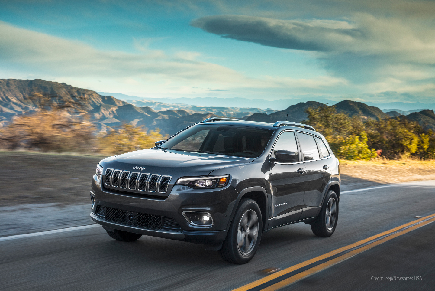 Jeep Cherokee on highway in front of mountains