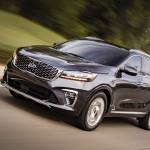 Kia Sorento SUV traveling on road beside trees
