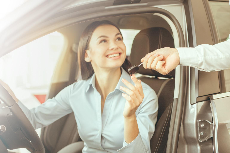 Woman in car receiving keys