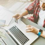 Man using laptop to improve credit score