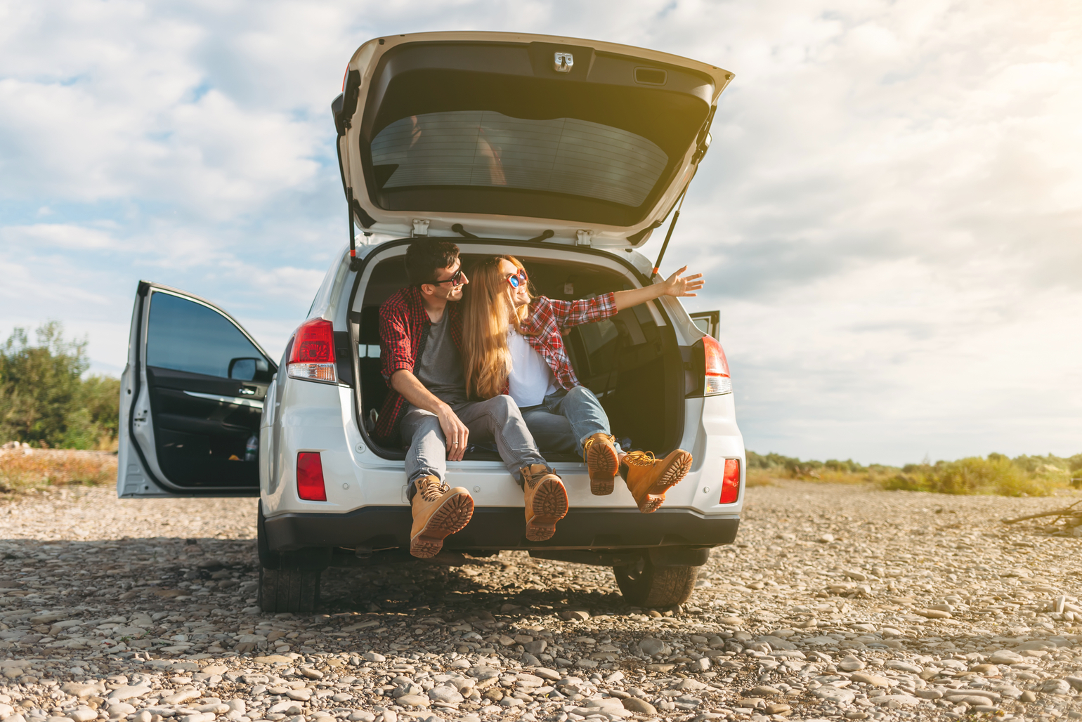 Couple sitting on tailgate of car
